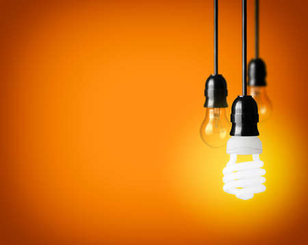 電球とオレンジ色の背景上のエネルギー セーバー電球 写真素材