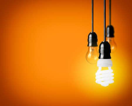Light bulbs and energy saver bulb on orange background