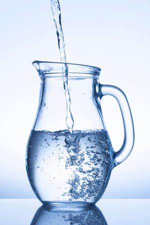 flowing water: Flowing water in a jug on blue