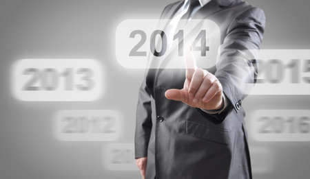 Businessman selects 2014 on touch screen Stock Photo