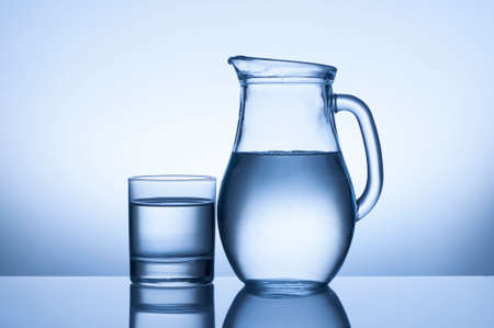 water glass and jug on blue background photo