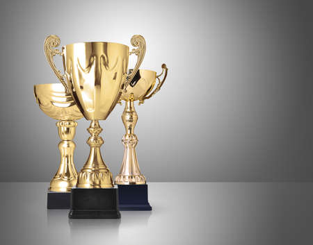 sports trophy: three different kind of golden trophies on gray background Stock Photo