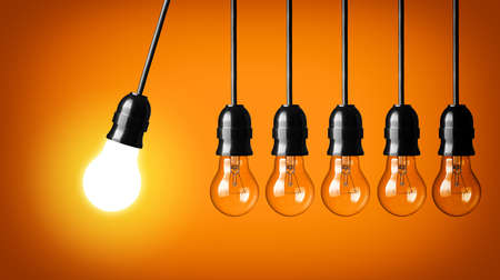 Idea concept on orange background  Perpetual motion with light bulbs