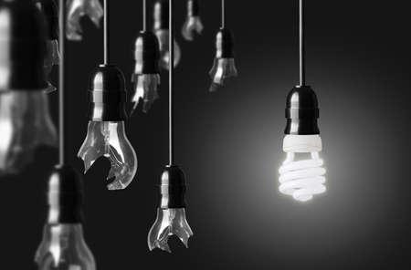 enchufe de luz: el concepto de idea con bombillas rotas y un brillante bombilla de ahorro de energía