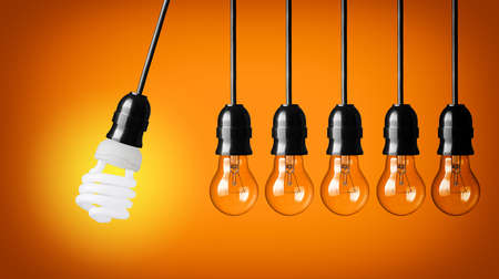 colliding: Perpetual motion with light bulbs and energy saver bulb  Idea concept on orange background