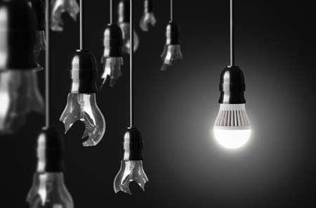 enchufe de luz: el concepto de idea con bombillas rotas y una bombilla LED que brilla intensamente