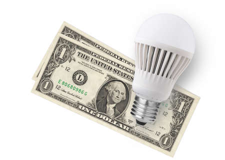 LED bulb over dollar bills isolated on white background photo