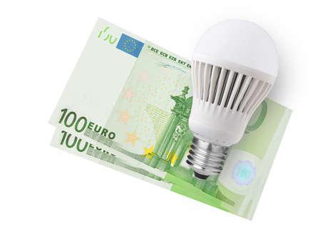 LED bulb over euro bills on white background