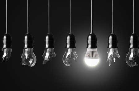 깨진 전구 및 한 빛나는 LED 전구 아이디어 개념