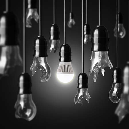 idea concept with broken bulbs and one glowing LED bulb Stock Photo