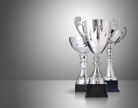 three different kind of silver trophies on gray background