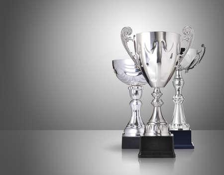 trofeo: tres tipos diferentes de trofeos de plata sobre fondo gris