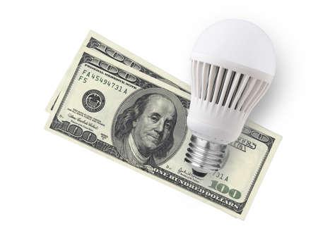 LED bulb over dollar bills isolated on white background photo
