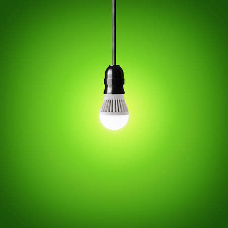 Glowing led bulb on green background