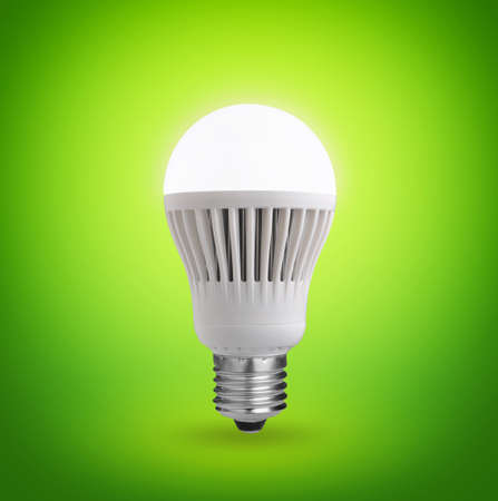 Glowing LED bulb on green background  Stock Photo
