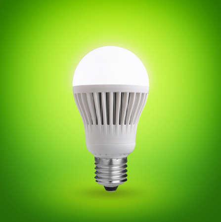 Leuchtende LED Glühbirne auf grünem Hintergrund