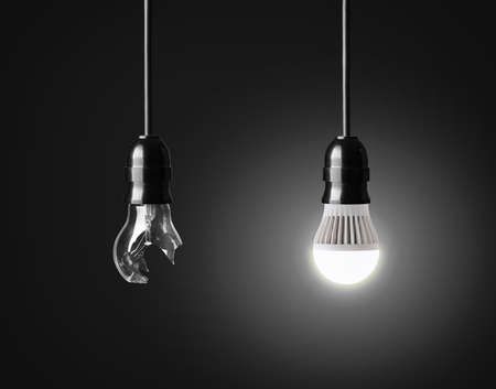 conserve: Broken light bulb and  glowing LED bulb on black Stock Photo