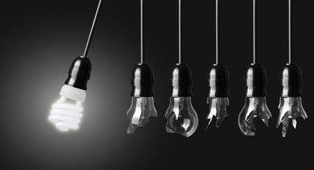 Perpetuum mobile met gebroken lampen en energy saver lamp Stockfoto