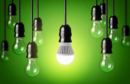 blue light: LED bulb and simple light bulbs Green background Stock Photo