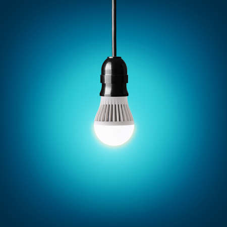 conserve: Glowing led bulb on blue background