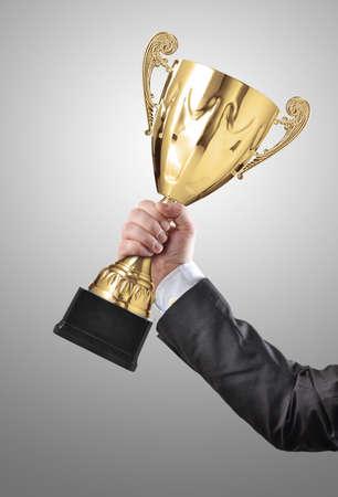 Businessman holding a champion golden trophy