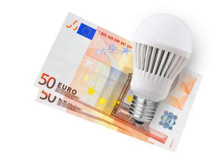 LED bulb over euro bills on white background photo