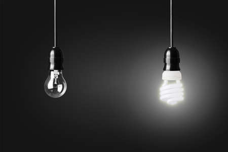 Light bulb and glowing energy saver bulb on black Stockfoto