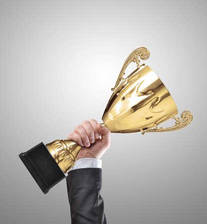 místo: Podnikatel drží zlatou trofej mistra na šedý Reklamní fotografie