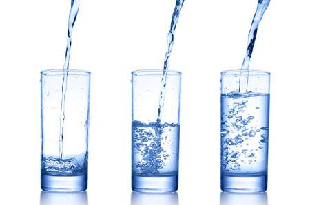 verser de l'eau dans un verre sur fond blanc