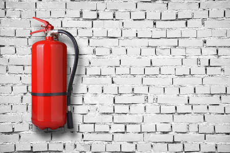fire extinguisher on white brick wall photo