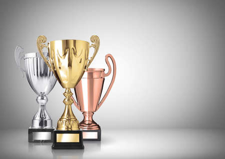 golden, silver and bronze trophies on gray background photo