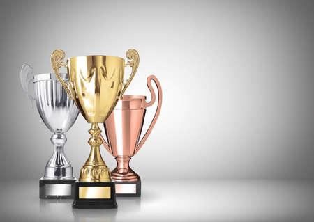 oro, plata y bronce trofeos en fondo gris Foto de archivo