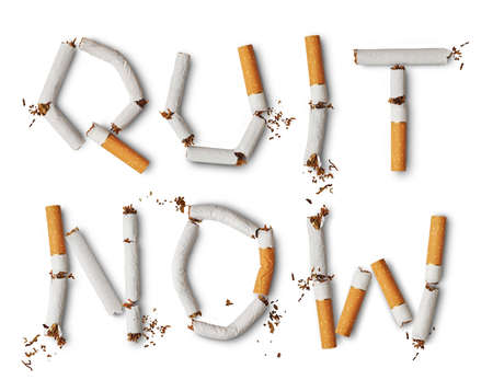 Text quit now made from broken cigarettes Stock Photo