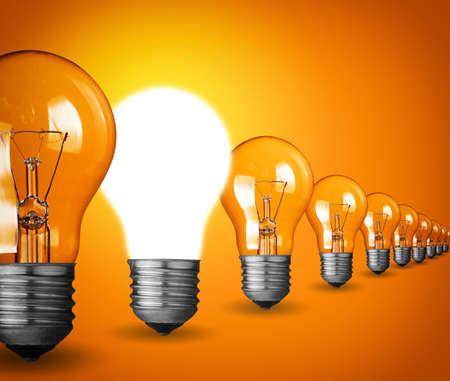 enchufe de luz: Concepto de la idea con bombillas de luz sobre fondo naranja
