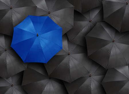 concept voor leiderschap met veel zwarten en blauwe paraplu