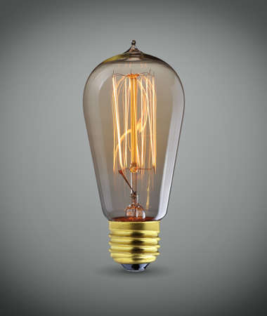 light color: Glowing vintage  light bulb over gray background Stock Photo