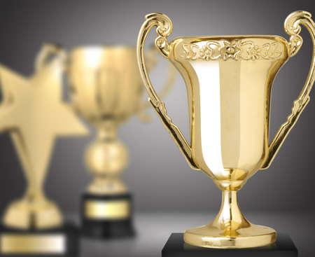 trofeo: trofeos de oro sobre fondo gris Foto de archivo