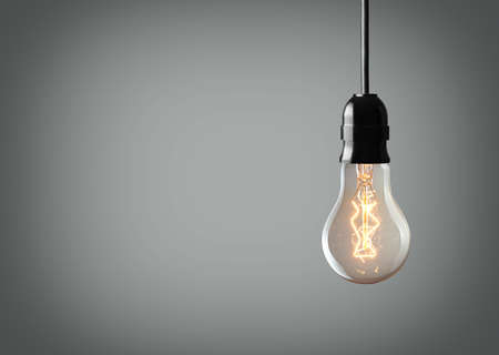 green light: Vintage hanging light bulb over gray background