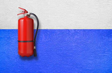 fire extinguisher on blue and white old wall Foto de archivo