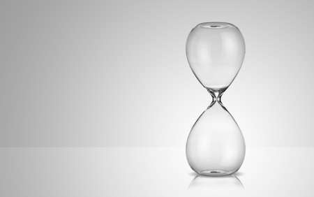 Empty hourglass on gray background