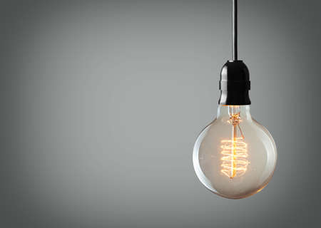 Vintage hanging light bulb over gray background