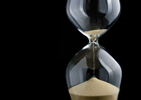 reloj de arena: Primer plano de reloj de arena en el fondo negro