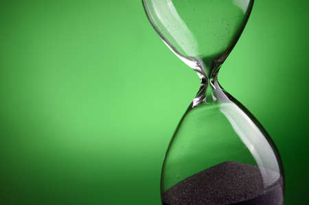 sand clock: Close-up hourglass on green background