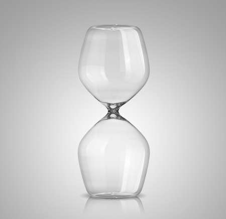 trickling: Empty hourglass on gray background