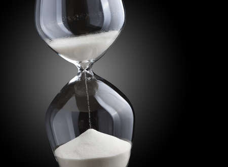 trickle: Closeup hourglass on black background