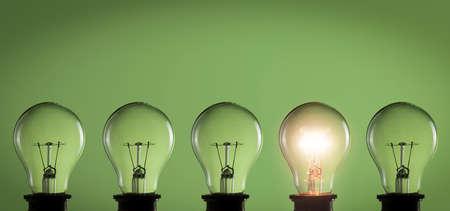 Idee, Konzept. Glühbirnen auf grünem Hintergrund Standard-Bild