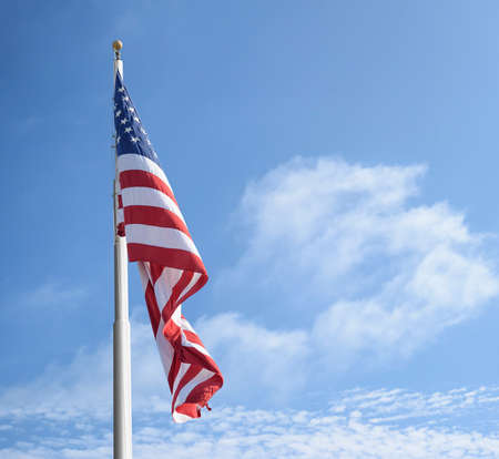 American flag on the pole against blue sky and clouds