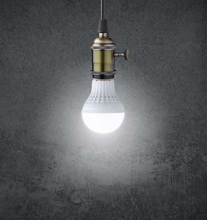 creativity and innovation: Glowing LED bulb on grunge wall