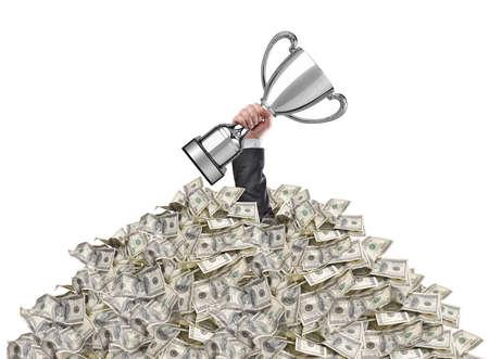 男の手が表面上カップ トロフィーを持ってお金の山で立ち往生 写真素材