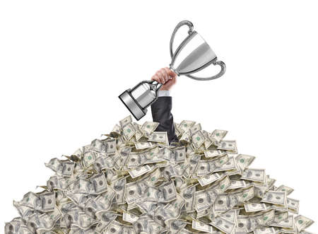hand of a man stuck in a pile of money holding a cup trophy above the surface Stock Photo